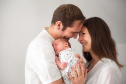 Babyfoto neugeborenes Baby schmust mit Mutter und Vater