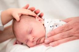 neugeborenes Baby schläft und wird von Ändern gehalten