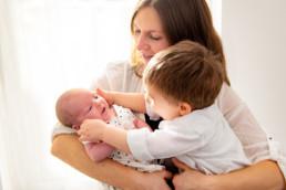 Babyfotografie neugeborenes Baby mit Mutter und Bruder