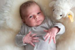 Foto Baby liegt auf eine Fell mit seinem Kuscheltier Schaf