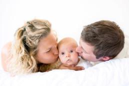 Foto Eltern küssen Baby von beiden Seiten auf die Wange