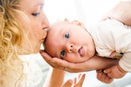 Foto Baby liegt auf dem Arm seines Vaters und Mutter küsst Baby