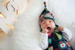 Babyfoto, Baby mit Zipfelmütze gähnt