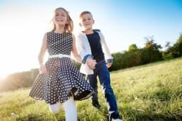 Geschwisterfoto , Bruder und Schwester laufen über eine Wiese