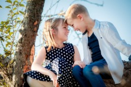 Geschwisterfoto , Bruder und Schwester sitzen auf einem Baum