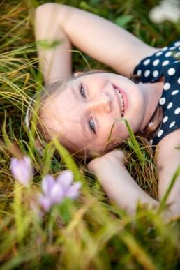 Kinderfoto, Mädchen liegt auf einer Wiese