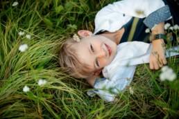 Kinderfoto, Junge liegt auf einer Wiese