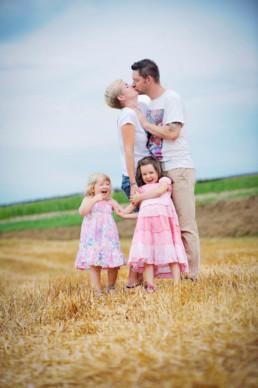 Familienfoto auf dem Feld, Eltern küssen, Kinder lachen