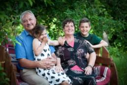 Familienfoto, Oma und Opa sitzen mit Enkeln auf einer Bank