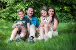 Familienfoto, Familie sitzt auf einer Wiese