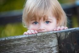 Kinderfoto Pforzheim Foto Kinder schaut über Zaun, Kinderaugen, Blick