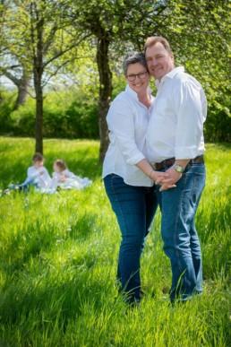 Foto Familienfoto Vater und Mutter im Vordergrund, Kinder im Hintergrund