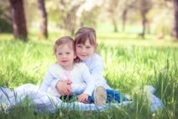 Foto zwei Mädchen sitzen auf einer Blumenwiese, Geschwisterfoto