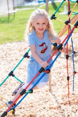 Foto Mädchen im Kindergarten auf Klettergerüst