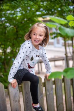 Foto Mädchen im Kindergarten klettert über Zaun