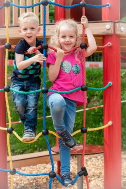 Foto Geschwister im Kindergarten auf Klettergerüst