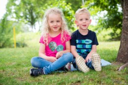 Foto Geschwister im Kindergarten sitzen im Garten