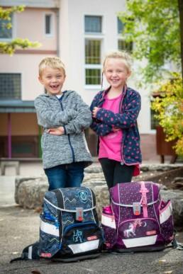 Foto Geschwister auf dem Schulhof mit Schulranzen