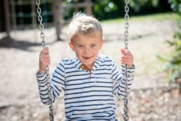 Foto lachendes Schulkind auf der Schaukel