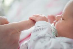 Foto schlafendes Baby hält den Finger seiner Mutter
