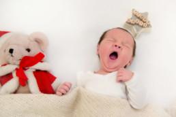 Foto neugeborenes Baby schläft mit Teddy unter einer gestrickten Decke und gähnt