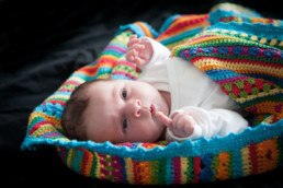 Foto, Baby liegt in eine bunte Decke gewickelt und zeugt mit dem Finger