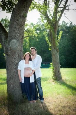 Schwangerschaftsfotos in Pforzheim Wurmberg, Schwangere und ihr Partner stehen an einem Baum, Sommerstimmung