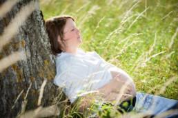 Schwangerschaftsfotografie in Pforzheim Wurmberg, schwangere Frau lehnt an einem Baum im Sommer