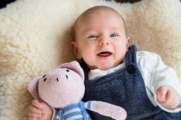 Foto Baby mit Kuscheltier lacht