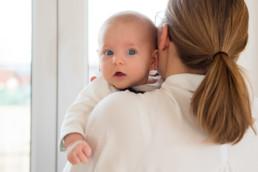 Foto Baby mit blauen Augen schaut über die Schulter seiner Mutter