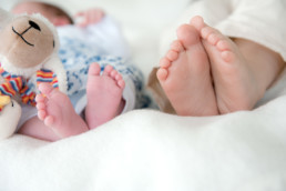 Foto Kinderfüsse, babyfüsse mit Kuscheltier, Geschwister