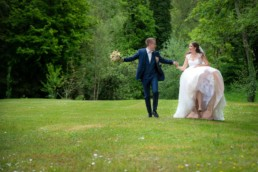 Foto Braut und Bräutigam laufen über eine Wiese