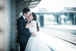 Foto Brautpaar am Bahnhof küsst sich