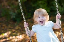 Foto Kind auf der Schaukel lacht