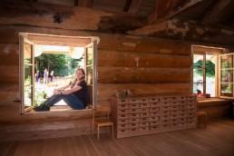 Kindergartenleiterin Annette Haug sitzt im Fenster des Blockhauses - Fotoprojekt Nur-so-halb von Stefanie Morlok Fotografin