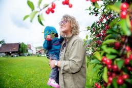 Tagesmutter Cathrin Daubenberger mit einem Tageskind im Garten in Gräfenhausen - Fotoprojekt Nur-so-halb von Stefanie Morlok Fotografin