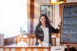 Luana Basoni in ihrem Restaurant Costa Smeralda mit der Speisekarte auf einer Tafel - Fotoprojekt Nur-so-halb von Stefanie Morlok Fotografin
