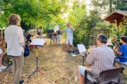 Orchesterleiter Thomas Meyer probt mit einer Bläsergruppen im sommerlichen Garten - Fotoprojekt Nur-so-halb von Stefanie Morlok Fotografin